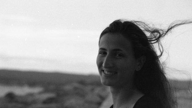 Frau Sanuy Suz steht im Vordergrund. Im Hintergrund ist verschwommen eine Landschaft zu sehen.