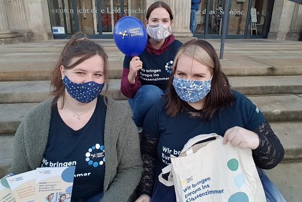 Drei junge Studentinnen sitzen auf einer Treppe und halten EmS-Give Aways und EmS-Flyer in die Höhe. Dabei tragen sie alle das EmS-T-Shirt und Masken.