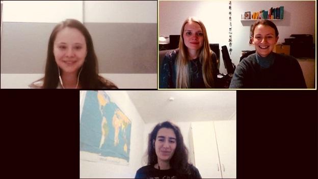 Auf dem Bild erkennt man vier junge Frauen, die in ihre Kamera lächeln.