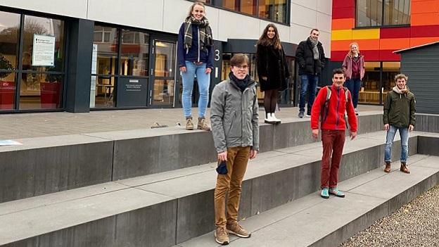 Sieben junge Studierende stehen auf einer Treppe und lächeln in die Kamera.