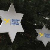 An einem Weihnachtsbaum hängen zwei weiße Holzsterne, auf welchen das EmS-Logo zu sehen ist.