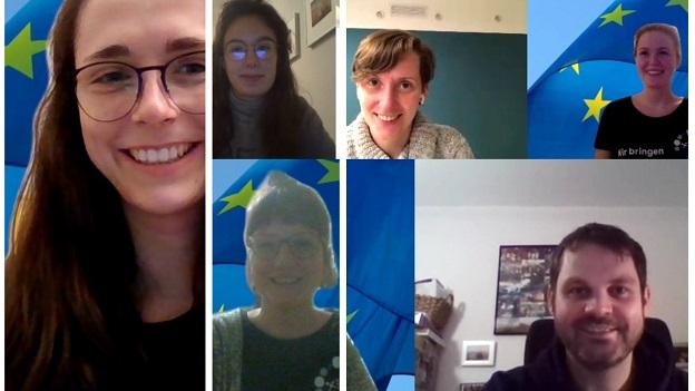 Auf dem Bild sieht man vier junge Studentinnen und zwei Lehrkräfte die lächelnd in die Kamera blicken. Im Hintergrund weht die EU-Flagge