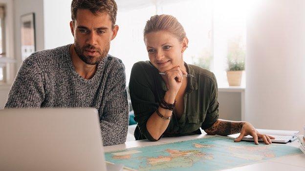 Junger Mann und junge Frau sitzen an einem Tisch, schauen gemeinsam in einen Laptop. Vor Ihnen auf dem Tisch liegt eine Weltkarte.