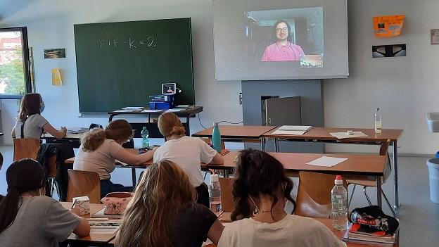 Schüler/-innen sitzen am Tisch und schreiben etwas auf, während vorne an der Leinwand ein junger Mann in die Kamera lächelt