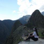 Eine peruanische Gaststudierende sitzt im Vordergrund auf einem Stein und blickt auf Machu Picchu im Hintergrund.