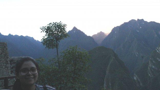 Porträtfoto einer peruanischen Gaststudierenden. Im Hintergrund ist eine Gebirgslandschaft zu sehen.