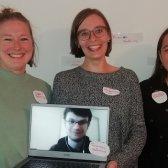 3 junge Frauen lächeln in die Kamera und halten den Laptop in die Höhe, auf dem eine weitere Person zu sehen ist.